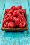 Fresh raspberry in a wooden plate. On blue background Stock Photography