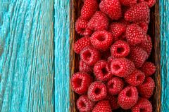 Fresh raspberry in a wooden plate. On blue background Stock Image