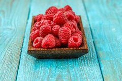 Fresh raspberry in a wooden plate. On blue background Stock Photos