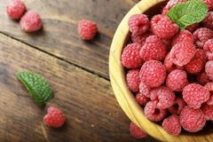 Fresh raspberry in a wooden plate. Ripe raspberries on a plate, close up Stock Image