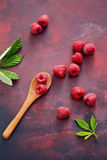 A fresh raspberry on a wooden spoon. Ripe fresh raspberries with leaves on rustic background Royalty Free Stock Photo