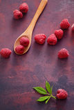 A fresh raspberry on a wooden spoon. Ripe fresh raspberries with leaves on rustic background Stock Images