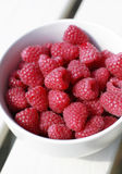 Fresh Rasperries. Fresh Organic Juicy Raspberries in white dessert bowl on garden table Royalty Free Stock Images