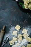 Fresh ravioli with flour. On dark stone background, top view. Cooking process Stock Photos