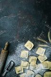 Fresh ravioli with flour. On dark stone background, top view. Cooking process royalty free stock photography