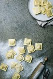 Fresh ravioli with flour. On dark stone background, top view. Cooking process Stock Photos