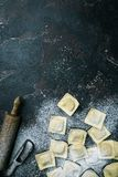 Fresh ravioli with flour. On dark stone background, top view. Cooking process stock photography