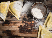 Fresh  ravioli and flour on rustic  wooden background. Top view Royalty Free Stock Images