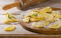 Fresh Ravioli on with flour  on a  wooden backround. Royalty Free Stock Photos