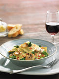 Fresh ravioli pasta. With grilled garlic, broccoli, mushroom and bacon bits. In blue bolw with red wine glass and sliced bread in background on wood table Stock Photos