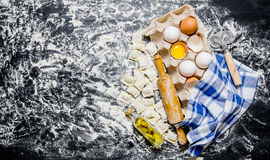 Fresh ravioli with a rolling pin, eggs and olive oil. On black table with flour. Free space for text . Top view Stock Photo