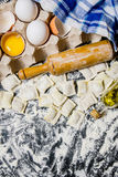 Fresh ravioli with a rolling pin, eggs and olive oil. On black table with flour. Top view Royalty Free Stock Photography
