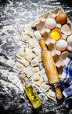 Fresh ravioli with a rolling pin, eggs and olive oil. On black table with flour. Top view Stock Image