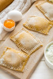 Fresh ravioli with spinach and ricotta waiting to be cooked. On wooden table. Selective focus Royalty Free Stock Images