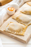 Fresh ravioli with spinach and ricotta waiting to be cooked. On wooden table. Selective focus Royalty Free Stock Photos