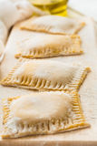 Fresh ravioli with spinach and ricotta waiting to be cooked. On wooden table. Selective focus Stock Photo