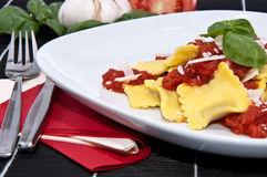 Fresh Raviolis on a plate (with ingredients). Fresh Raviolis on a plate with raw ingredients in the background on a black tablecloth Stock Image