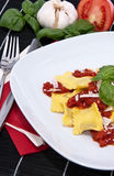 Fresh Raviolis on a plate (with ingredients). Fresh Raviolis on a plate with raw ingredients in the background on a black tablecloth Stock Images