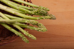 Fresh raw asparagus in basket. On wooden background Royalty Free Stock Photos