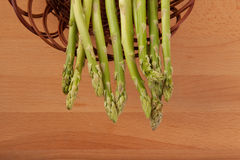 Fresh raw asparagus in basket. On wooden background Stock Images