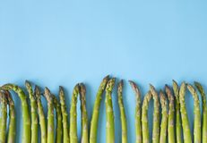 Fresh  raw asparagus on light blue background. Fresh  raw asparagus on light blue background, copy space Royalty Free Stock Photo