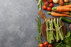 Fresh raw asparagus and other spring vegetables. Cooking in the kitchen, top view Royalty Free Stock Photos