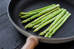 Fresh raw asparagus in a pan. Black background, top view, space for text. stock image