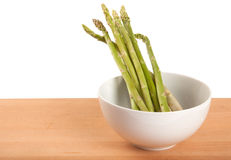 Fresh raw asparagus in white bowl. On wooden background Stock Photo