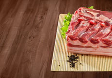 Fresh and raw bacon ribs on kitchen table ready for bbq or grill. With clipping path Stock Image