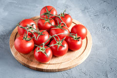 Fresh raw and beautiful grape tomatoes for use as cooking ingredients Tomatoes on wooden board. Fresh grape tomatoes with basil and coarse salt for use as Stock Image