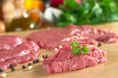 Fresh Raw Beef. Meat with parsley on top, with vegetables, herbs and kitchen utensils in the back (Selective Focus, Focus on the front of the meat and the Stock Photos