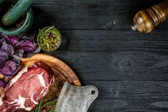 Fresh raw beef with basil and a sprig of rosemary with ax for meat on black wooden background. Top view. Fresh raw beef with spices, fresh basil and a sprig of Stock Image