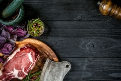 Fresh raw beef with basil and a sprig of rosemary with ax for meat on black wooden background. Top view. Fresh raw beef with spices, fresh basil and a sprig of Royalty Free Stock Photos