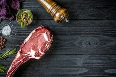 Fresh raw beef with basil and a sprig of rosemary on black wooden background. Fresh raw beef with spices, fresh basil and a sprig of rosemary on black wooden Royalty Free Stock Photography