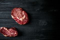 Fresh raw beef on black wooden background. Top view. Still life. Copy space. Flat lay Royalty Free Stock Images