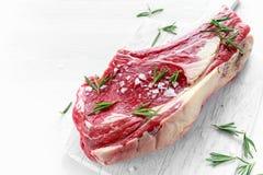 Fresh Raw Beef bone rib roughly choppid on white board with herbs Stock Photos