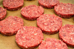 Fresh raw beef burger patties on paper background. Fresh raw juicy unprepared beef burger patties on brown paper background Stock Photos