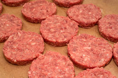 Fresh raw beef burger patties on paper background. Fresh raw juicy unprepared beef burger patties on brown paper background Stock Photo