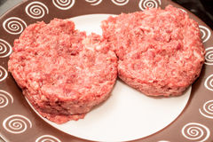 Fresh raw beef burger patties on plate. Fresh raw juicy unprepared beef burger patties on brown plate Stock Photo