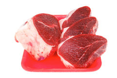 Fresh raw beef. Butchery : fresh raw beef lamb big fillet mignon ready to cooking on red tray isolated over white background Stock Photos