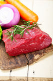 Fresh raw beef cut ready to cook. With vegetables and herbs Stock Photography