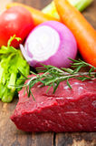 Fresh raw beef cut ready to cook. With vegetables and herbs Royalty Free Stock Photography