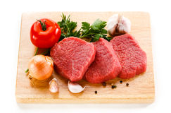 Fresh raw beef on cutting board. Fresh beef and vegetables on white background Royalty Free Stock Photos