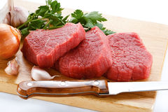 Fresh raw beef on cutting board. Fresh beef and vegetables on white background Royalty Free Stock Images