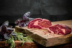 Fresh raw beef on cutting board with fresh basil and a sprig of rosemary Stock Image