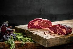 Fresh raw beef on cutting board with fresh basil and a sprig of rosemary Stock Photos