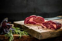 Fresh raw beef on cutting board with fresh basil and a sprig of rosemary Stock Images