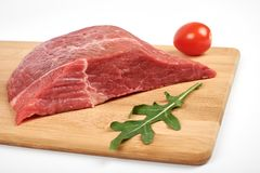 Fresh raw beef on a cutting board isolated on white background.  Royalty Free Stock Photo