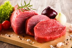 Fresh raw beef on cutting board and vegetables. On wooden table Royalty Free Stock Photo
