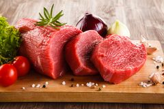 Fresh raw beef on cutting board and vegetables. On wooden table Royalty Free Stock Photography